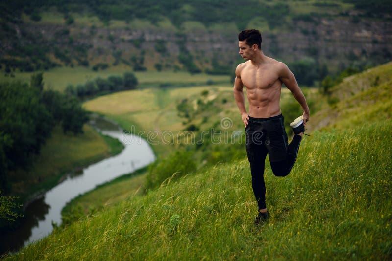 Geschikte atleet, spier, abs die, jonge mens uitrekkende oefeningen doen vóór training buiten op bos, rivierachtergrond stock foto
