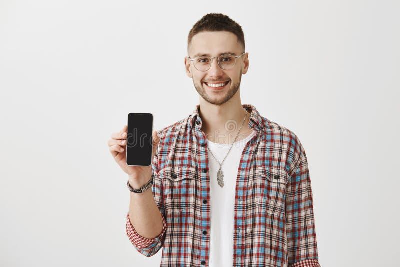 Geschikte en functionele smartphone Portret van knappe gebaarde model het tonen cellphone bij camera en ruim het glimlachen stock afbeelding