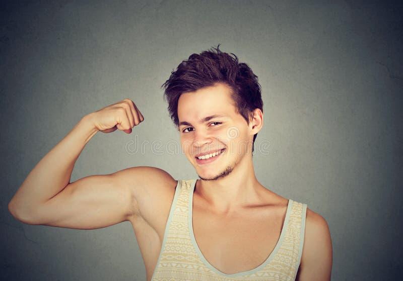 Geschikte en spier jonge mens die zijn bicepsen buigen royalty-vrije stock foto