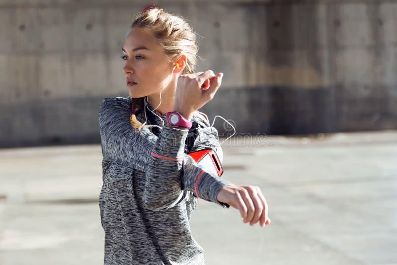 Geschikte en sportieve jonge vrouw die het uitrekken in stad doen zich royalty-vrije stock foto's