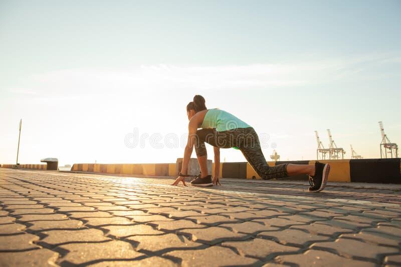 Geschikte en zekere vrouw in beginnende positie klaar voor het lopen Vrouwelijke atleet ongeveer om een sprint te beginnen weg te stock foto's