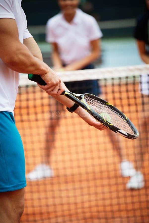 Geschikte gelukkige mensen die tennis samen spelen Het concept van de sport stock foto's