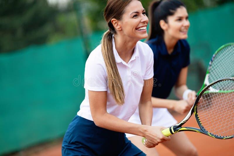 Geschikte gelukkige mensen die tennis samen spelen Het concept van de sport royalty-vrije stock fotografie