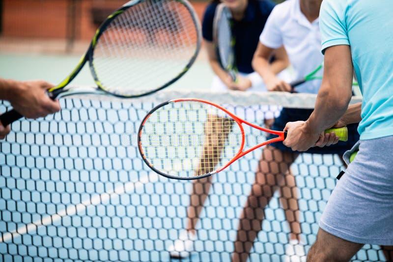 Geschikte gelukkige mensen die tennis samen spelen Het concept van de sport royalty-vrije stock foto's