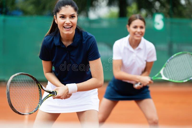 Geschikte gelukkige mensen die tennis samen spelen Het concept van de sport stock afbeelding