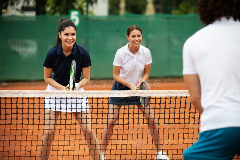 Geschikte gelukkige mensen die tennis samen spelen Het concept van de sport stock foto