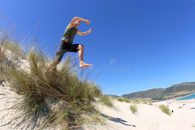 Geschikte, gezonde midden oude mens die over zandduinen springen stock afbeelding