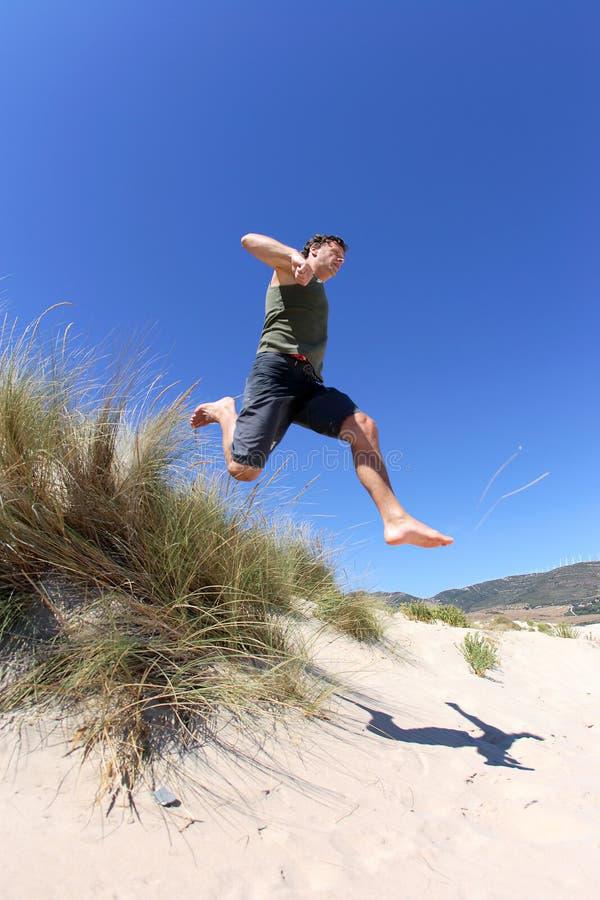 Geschikte, gezonde midden oude mens die over zandduinen springen stock fotografie