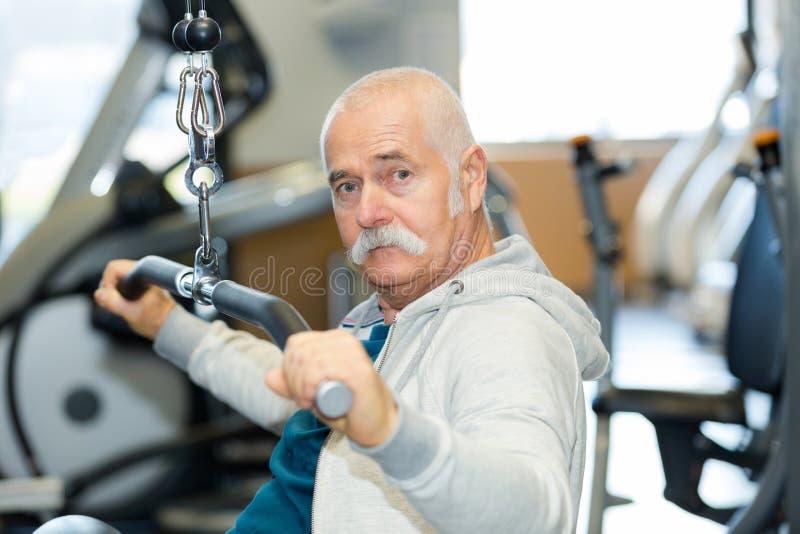 Geschikte hogere mens die bij gymnastiekclub uitwerken stock fotografie