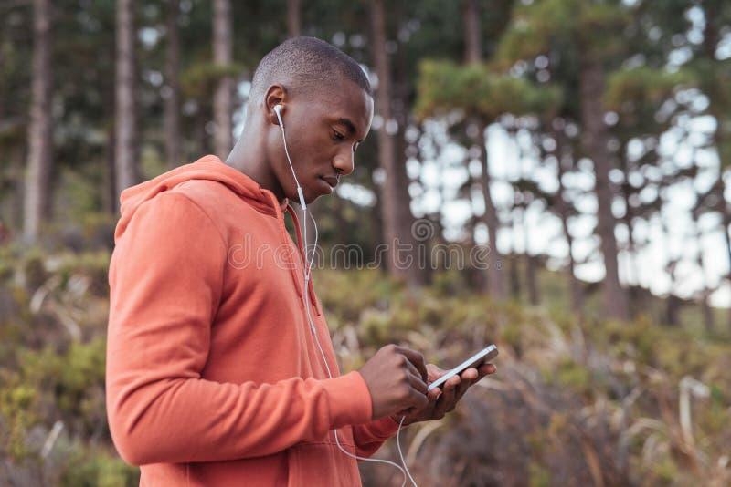 Geschikte jonge Afrikaanse mens die aan muziek vóór een looppas luisteren royalty-vrije stock fotografie