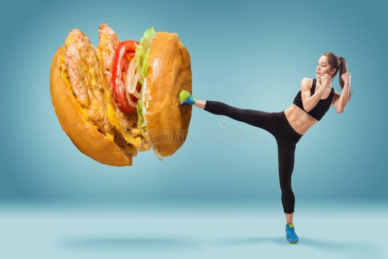Geschikte, jonge, energieke vrouwen in dozen doende hamburger als ongezond voedsel stock afbeeldingen