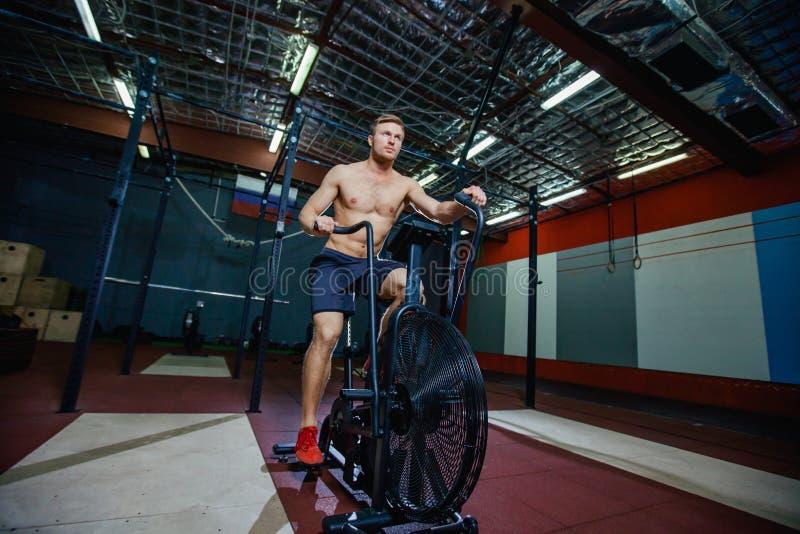 Geschikte jonge mens die hometrainer met behulp van bij de gymnastiek Fiets van de geschiktheids de mannelijke gebruikende lucht  royalty-vrije stock afbeeldingen