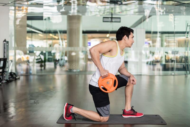 Geschikte jonge mens die met een gewichtsplaat tijdens hoger-lichaamstraining uitoefenen stock foto