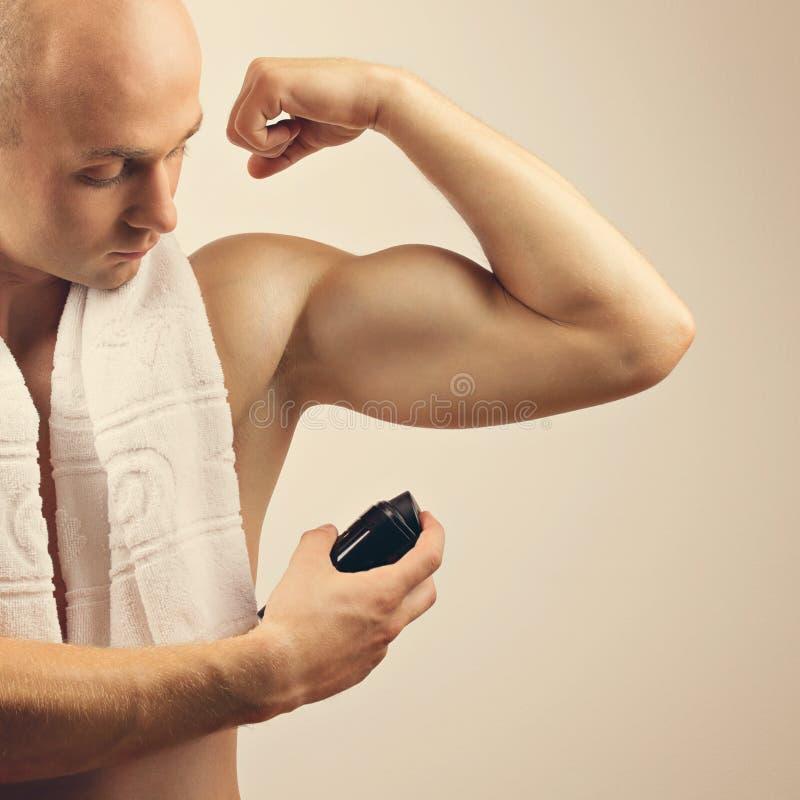 Geschikte jonge mens die transpiratiewerende neveldeodorant toepassen stock afbeeldingen