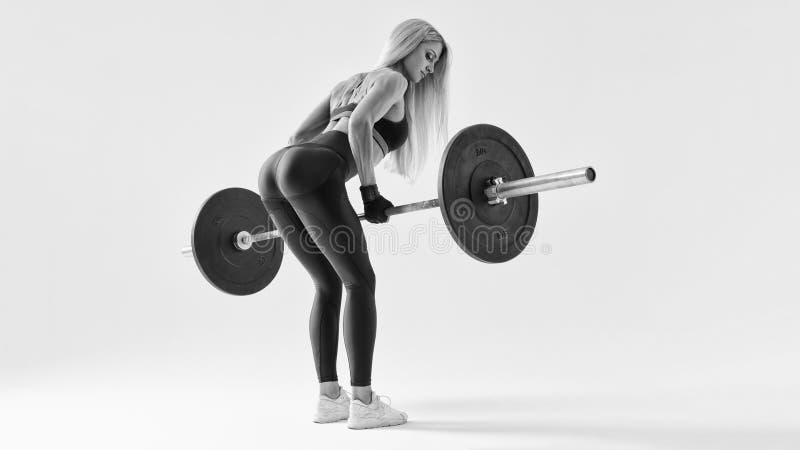 Geschikte jonge vrouw die barbell opheffen stock fotografie