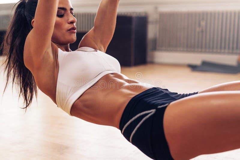 Geschikte jonge vrouw die bij gymnastiek uitoefenen stock afbeeldingen