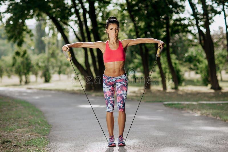 Geschikte jonge vrouw die duw op oefening in het park doen bij sunse Sportmotivatie Het concept van de gezondheid stock foto
