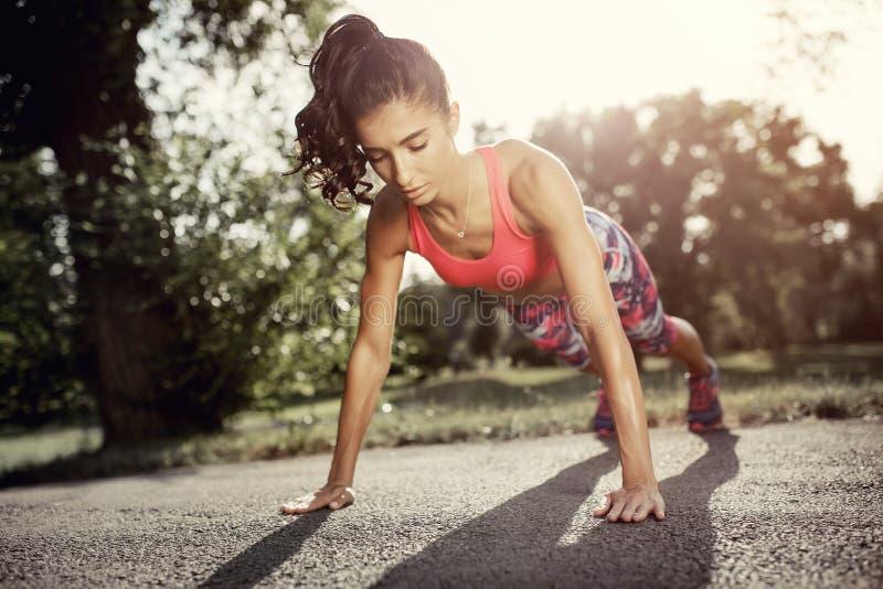 Geschikte jonge vrouw die duw op oefening in het park doen bij sunse Sportmotivatie Het concept van de gezondheid stock fotografie