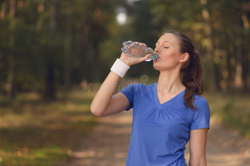 Geschikte jonge vrouw die gebotteld water drinken royalty-vrije stock foto's