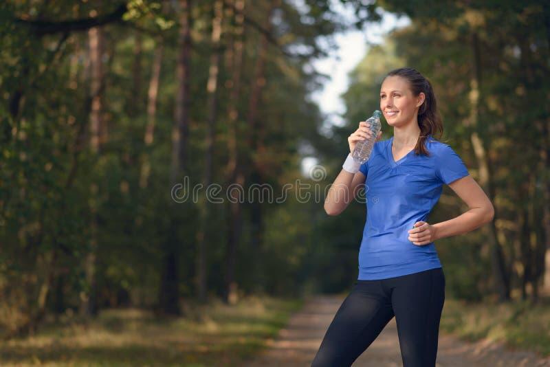 Geschikte jonge vrouw die gebotteld water drinken royalty-vrije stock foto