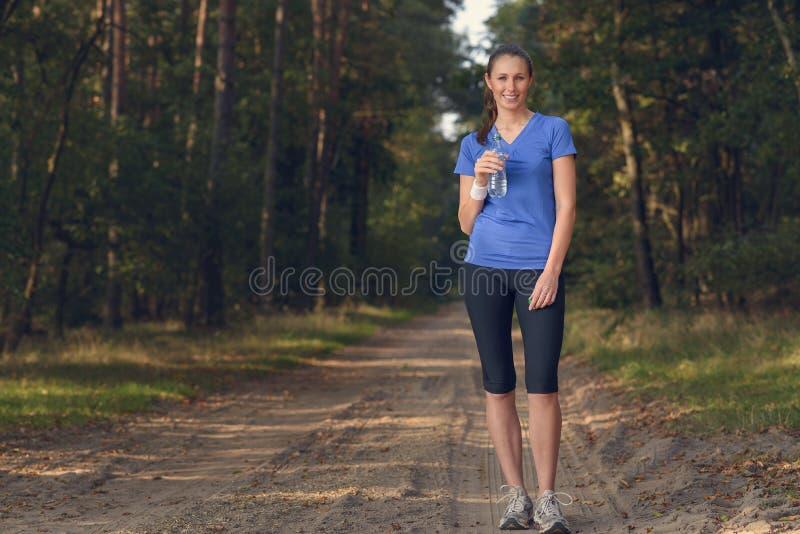 Geschikte jonge vrouw die gebotteld water drinken stock fotografie