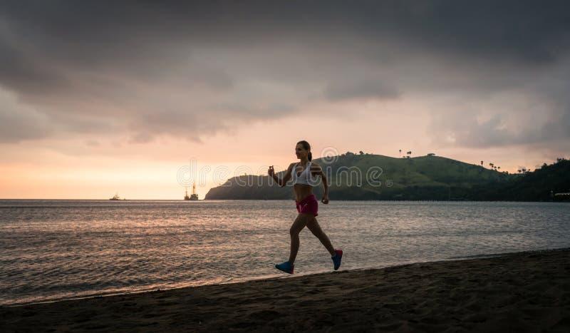 Geschikte jonge vrouw die op het strand tijdens de zomervakantie lopen in Flores-Eiland stock foto's