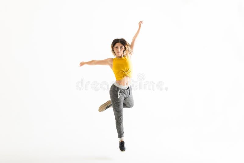 Geschikte Jonge Vrouw die over Witte Achtergrond dansen royalty-vrije stock afbeelding