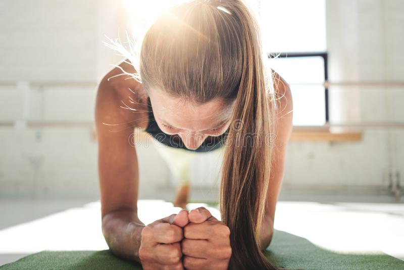 Geschikte jonge vrouw die planktraining doen om haar abs te verbeteren Wijfje in de gymnastiek die crossfit doen royalty-vrije stock fotografie