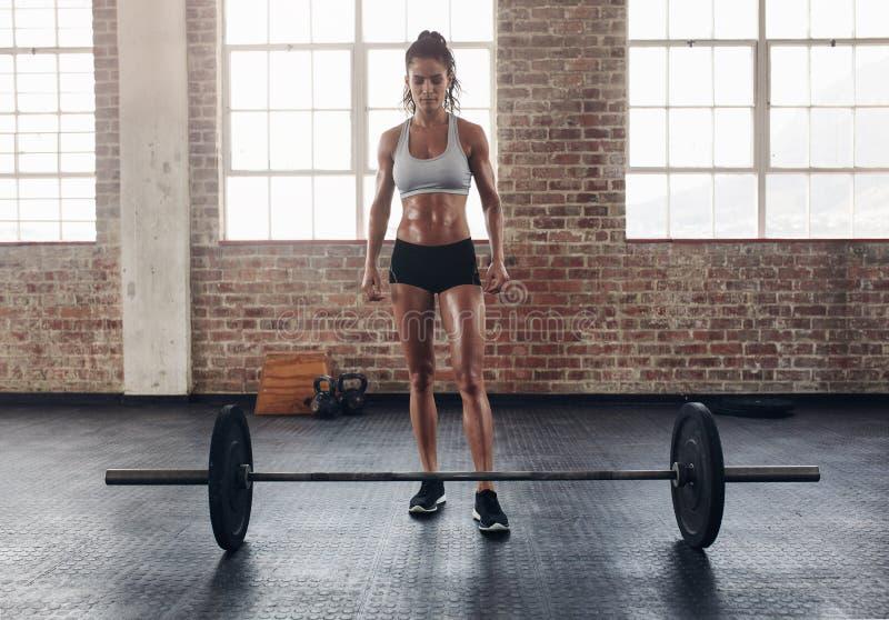 Geschikte jonge vrouw die zich bij gymnastiek met barbells op vloer bevinden royalty-vrije stock afbeeldingen