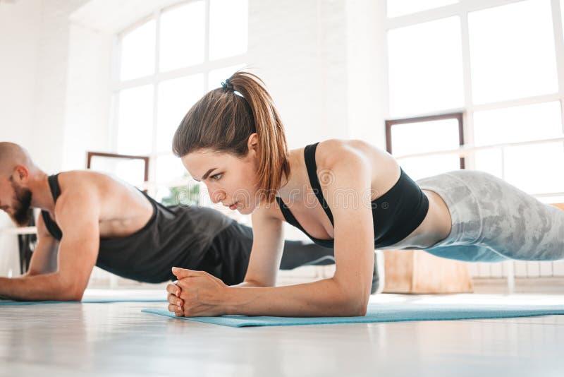 Geschikte jonge vrouw en man werkende abs die in witte binnenlandse gymnastiek uitoefenen stock afbeeldingen
