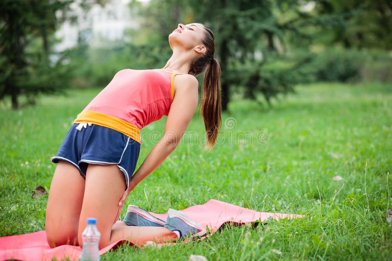 Geschikte jonge vrouw het praktizeren yoga in een stadspark, die Tibetaanse rite nummer drie doen stock foto
