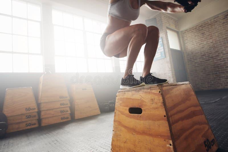 Geschikte jonge vrouwendoos die bij een crossfitgymnastiek springen royalty-vrije stock fotografie