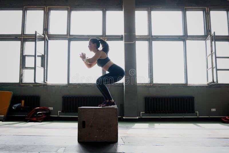 Geschikte jonge vrouwendoos die bij een gymnastiek van de crossfitstijl springen De vrouwelijke atleet voert doossprongen bij gym stock afbeeldingen