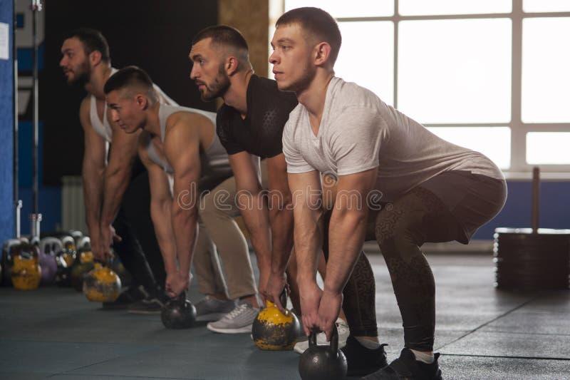 Geschikte Jongeren die met Kettlebells in Gymnastiek uitoefenen royalty-vrije stock foto's