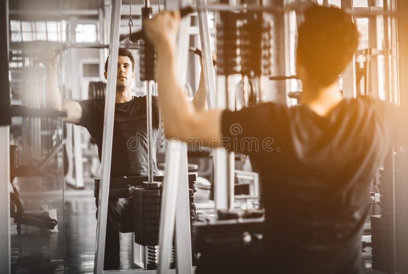 Geschikte Kaukasische knappe en grote spiertraining in sportkleding Jonge mensenoefening met machine in een gymnastiek stock afbeeldingen