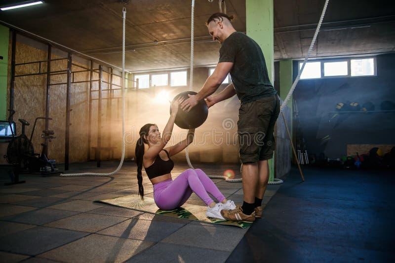 Geschikte Kaukasische vrouw die buikbaloefening met persoonlijke trainer in de gymnastiek doen royalty-vrije stock afbeelding