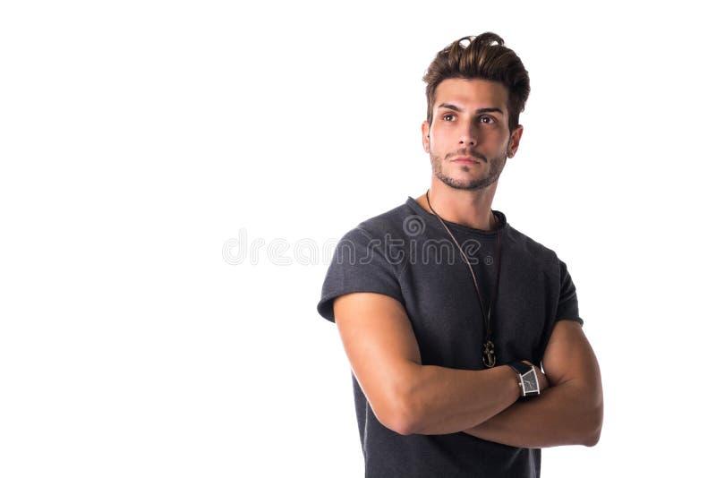 Geschikte knappe jonge mens zeker met gekruiste wapens, omhoog kijkend stock foto