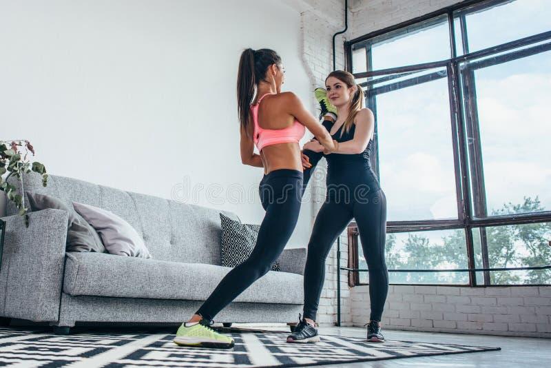 Geschikte meisjes die benentraining voorbereiden Been het uitrekken zich de vrouw die van de oefeningsgeschiktheid opwarming doen stock afbeelding