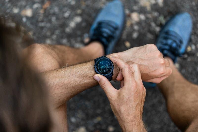 Geschikte mens die de slimme sport van de horloge wearable technologie smartwatch buiten controleren op fitness looppasgang Hoogs stock afbeeldingen