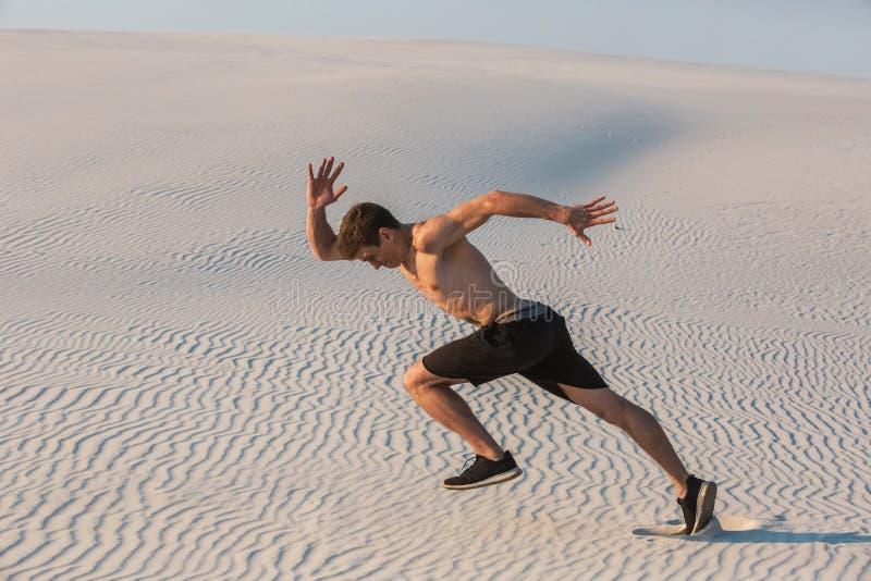 Geschikte mens die snel op het zand lopen Krachtige agent opleiding openlucht op de zomer stock fotografie