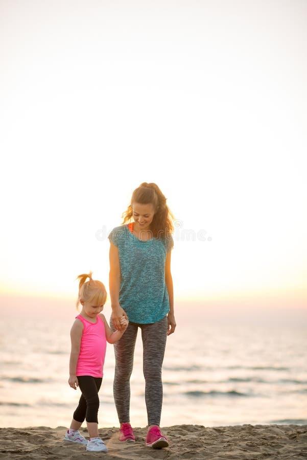 Geschikte moeder en dochter die en handen op strand lopen houden stock afbeelding