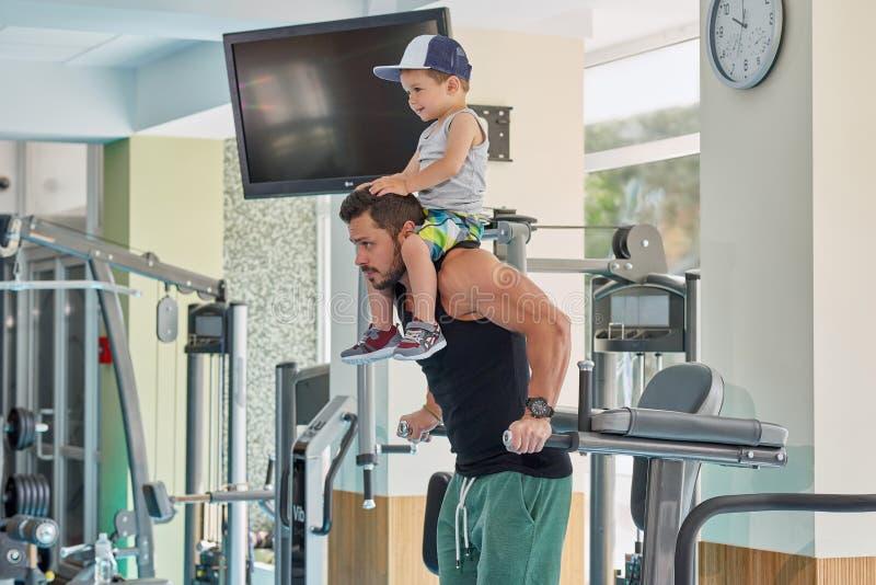 Geschikte sportman opleiding op gymnastiek` s simulator die weinig zoon op hals houden royalty-vrije stock fotografie