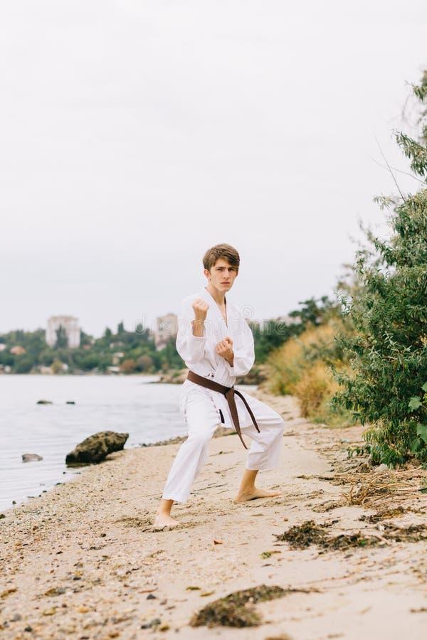 Geschikte, sterke, jonge mens het praktizeren judo op een natuurlijke achtergrond Traditioneel karate eenvormig concept stock foto's