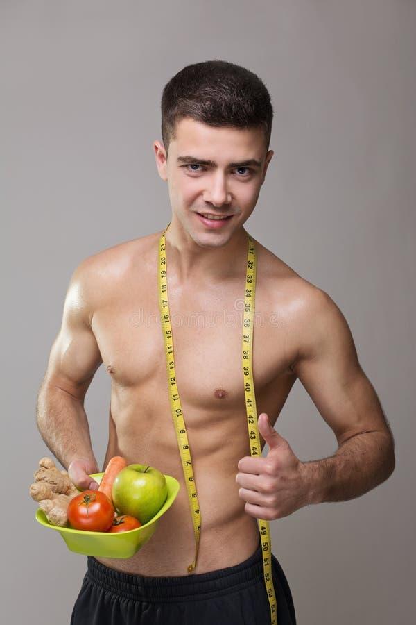 Geschikte veganistmens met het meten van band en gezond voedsel stock foto's