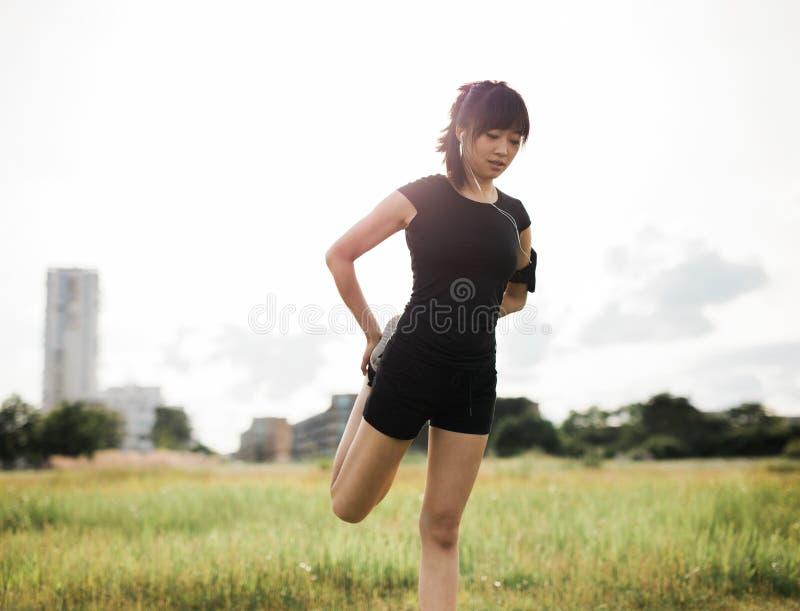 Geschikte vrouw die haar benen uitrekken bij stedelijk park royalty-vrije stock foto's