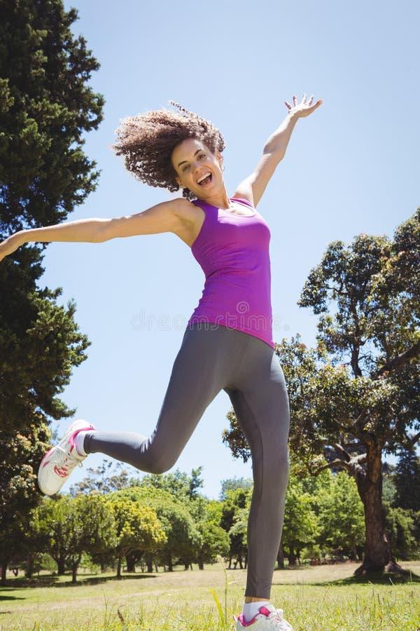Geschikte vrouw die in het park springen royalty-vrije stock afbeelding