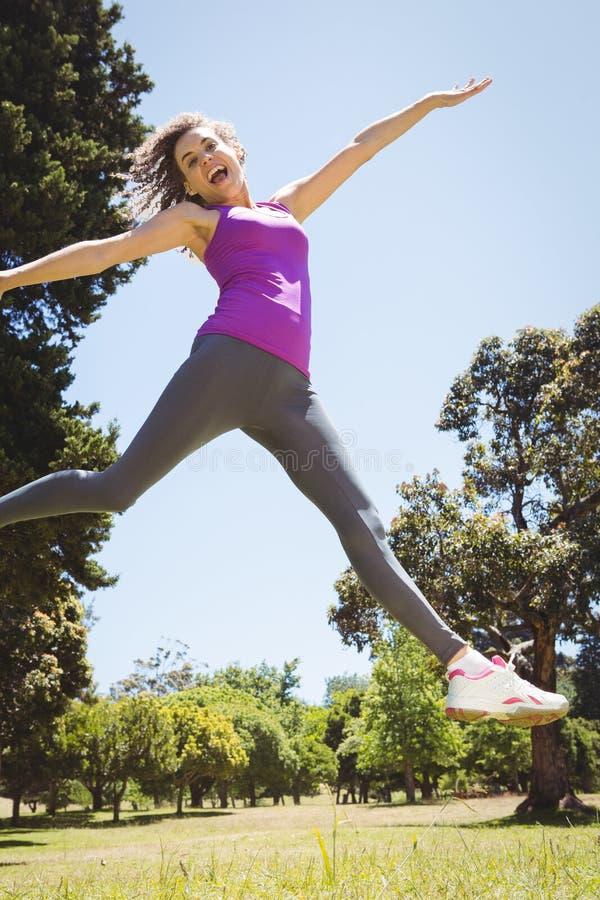 Geschikte vrouw die in het park springen stock foto