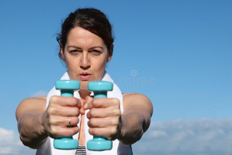 Geschikte vrouw die met gewichten uitoefent stock afbeeldingen