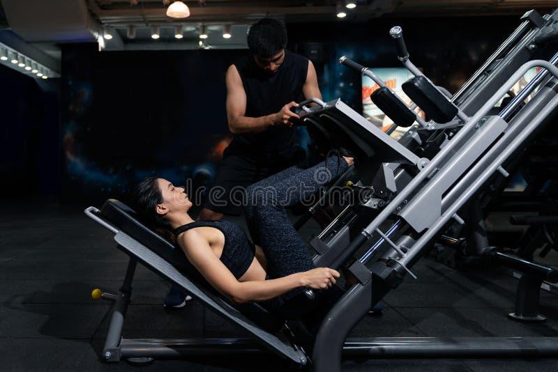 Geschikte vrouw die met trainer bij de gymnastiek uitwerken, Vrouw die spier opleiding doen bij de gymnastiek Atleet die bij de g royalty-vrije stock afbeeldingen