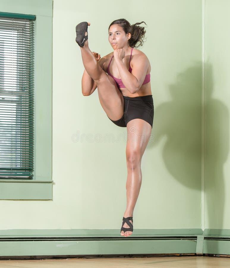 Geschikte Vrouw die Mid Air schoppen stock afbeeldingen